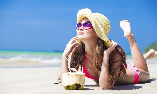 young woman smiling lying in straw hat in sunglasses with coconu